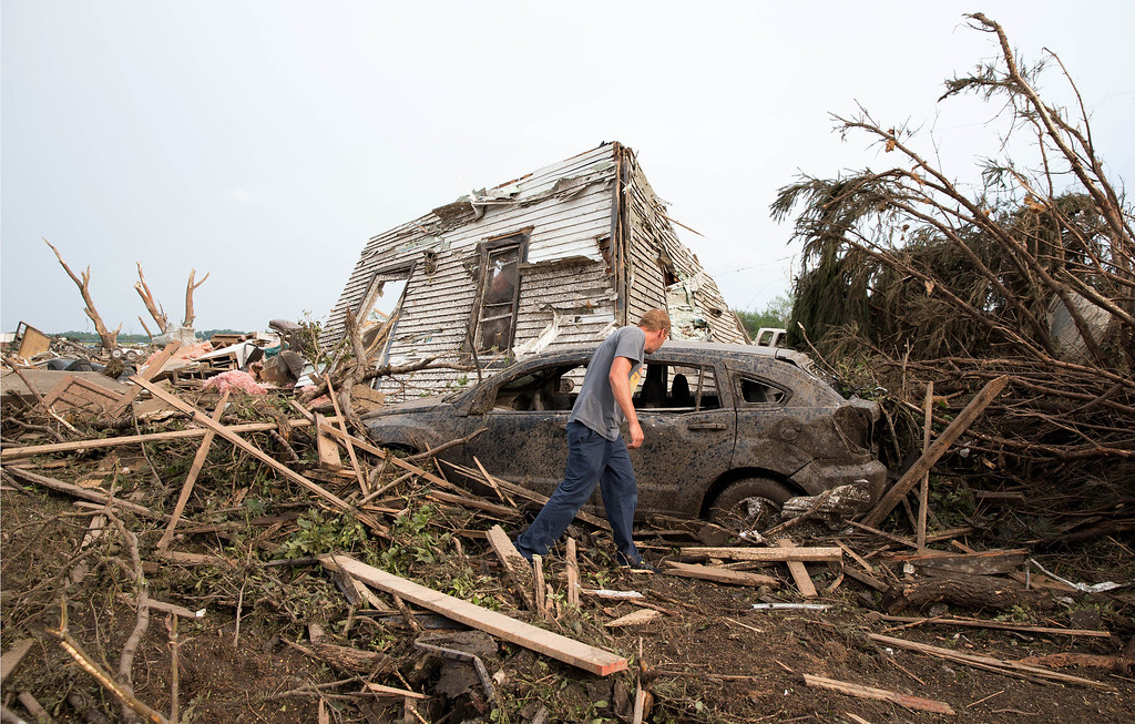 Description of . Tim Nelson  searches for survivors in Pilger, Neb.,  after the town was hit by a tornado Monday June 16, 2014.  Ast least one person has died due to the storm.  (AP Photo/The Omaha World-Herald/Ryan Soderlin)