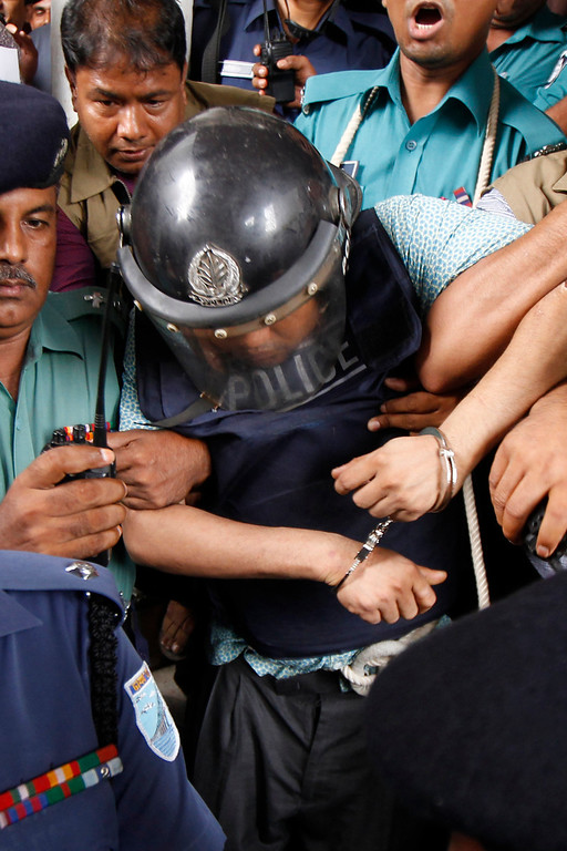 Description of . Bangladeshi property tycoon Sohel Rana (C), seen wearing police-issue body armor and helmet, is escorted for his appearance at the High Court in Dhaka on April 30, 2013.  AFP PHOTO/STRSTRDEL/AFP/Getty Images