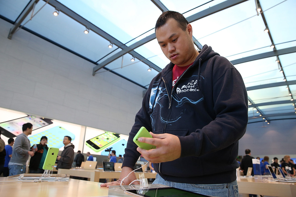 Description of . An Apple Store customer looks at the new Apple iPhone 5C at an Apple Store on September 20, 2013 in Palo Alto, California.   (Photo by Justin Sullivan/Getty Images)