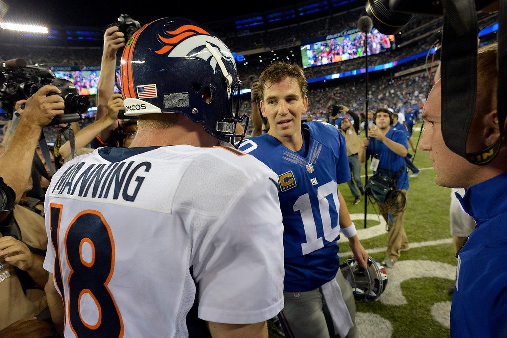 Description of . Denver Broncos quarterback Peyton Manning (18) meets with his brother New York Giants quarterback Eli Manning (10) at the end of the game September 15, 2013 MetLife Stadium. The Denver Broncos defeat the New York Giants 41-23. (Photo by John Leyba/The Denver Post)