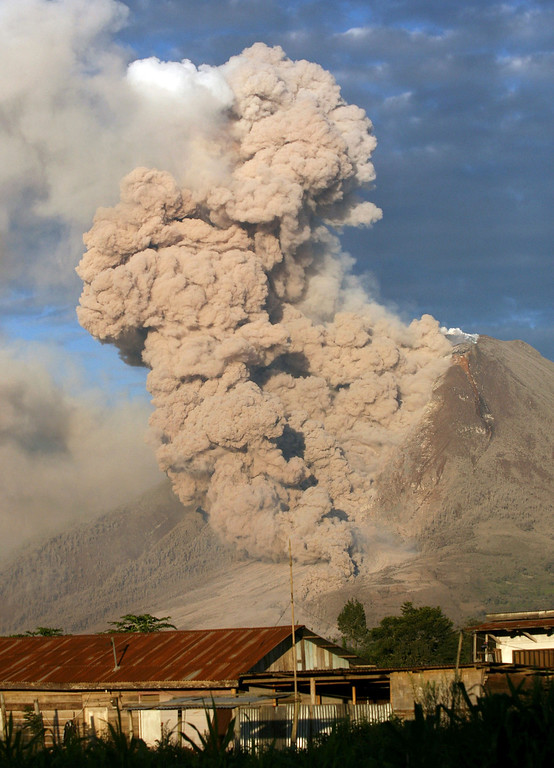 Description of . Mount Sinabung releases pyroclastic flows during an eruption as seen from Perteguhan, North Sumatra, Indonesia, Monday, Jan. 6, 2014. The 2,600-meter (8,530-foot) volcano has sporadically erupted since September. Authorities extended a danger zone around a rumbling volcano in western Indonesia on Sunday after it spewed blistering gas farther than expected, sending panicked residents streaming down the sides of the mountain. (AP Photo/Binsar Bakkara)