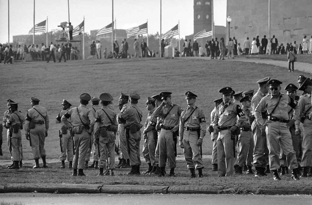 Description of . Army military policemen line up at Washington Monument grounds for duty during the March on Washington, August 28, 1963. In background are some of the early arrivals for the civil rights demonstration. (AP Photo)