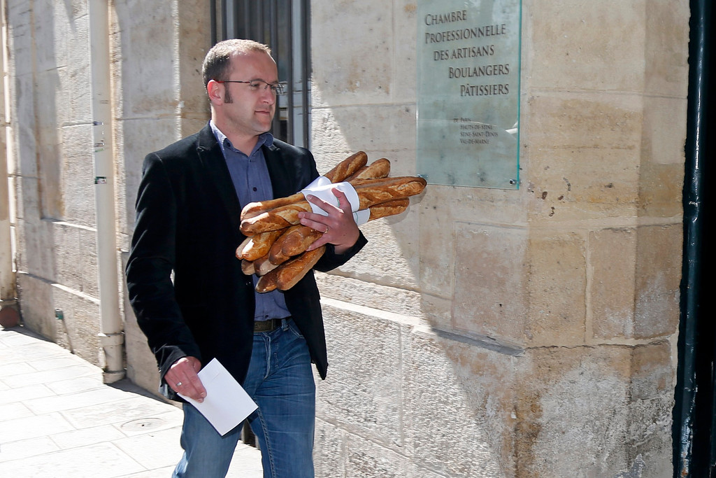 Description of . A baker carries an armful of baguettes, French bread, as he arrives to compete for the 'Grand Prix de la Baguette de la Ville de Paris' (Best Baguette of Paris 2013) annual prize at the Chambre Professionnelle des Artisans Boulangers Patissiers in Paris April 25, 2013. The baguette is a French cultural symbol par excellence and the competition saw 203 Parisian bakers who compete for recognition as finest purveyor of one of France's most iconic staples. The baguettes are registered, given anonymous white wrappings and an identification number. They are then carefully weighed and measured to ensure they do not violate the contest's strict rules. 52 entries were withdrawn for failing to measure between 55-70cm long or not matching the acceptable weight of between 250-300g. Every year, the winner earns the privilege of baking bread for the French President.   REUTERS/Charles Platiau