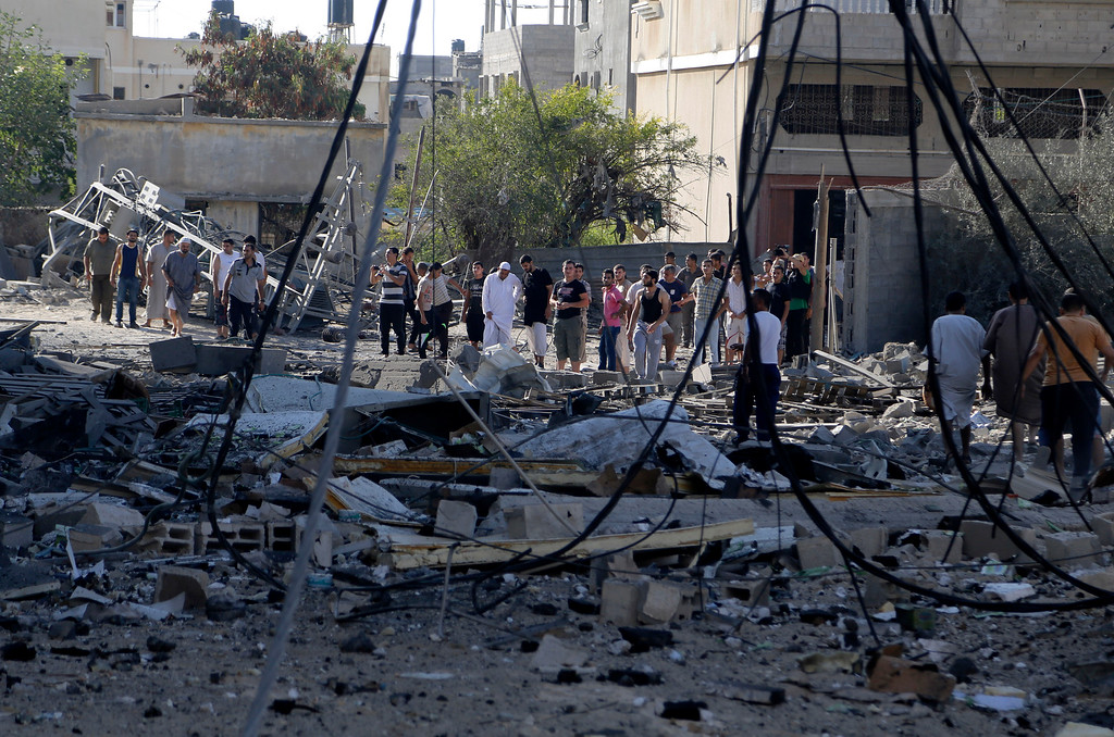 Description of . Palestinian inspects the damage of a destroyed milk factory after it was hit by an Israeli airstrike in Gaza City, Thursday, July 31, 2014. (AP Photo/Hatem Moussa)