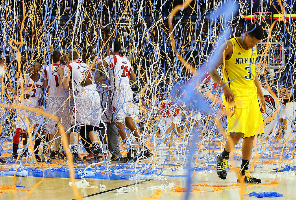 Description of . Michigan guard Trey Burke (3) walks off the court as confetti falls on Louisville players, including Russ Smith (2), Luke Hancock (11), Stephan Van Treese (44) and Zach Price (25), after the NCAA Final Four tournament college basketball championship game, Monday, April 8, 2013, in Atlanta. Louisville won 82-76. (AP Photo/Atlanta Journal-Constitution, Curtis Compton)