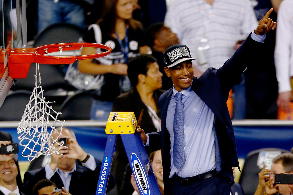 Description of . ARLINGTON, TX - APRIL 07:  Head coach Kevin Ollie of the Connecticut Huskies acknowledges the crowd after defeating the Kentucky Wildcats 60-54 in the NCAA Men\'s Final Four Championship at AT&T Stadium on April 7, 2014 in Arlington, Texas.  (Photo by Tom Pennington/Getty Images)