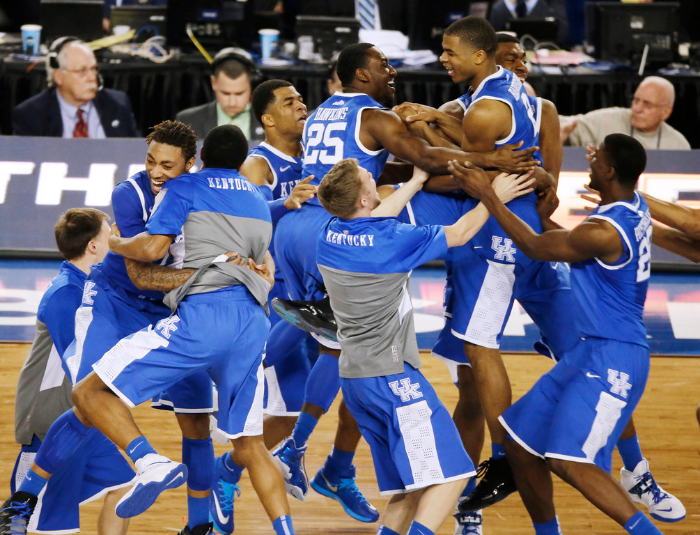 Description of . Kentucky celebrates after guard Aaron Harrison made a three-point basket in the final seconds against Wisconsin to win the game 74-73 during their NCAA Final Four tournament college basketball semifinal game Saturday, April 5, 2014, in Arlington, Texas. (AP Photo/Tony Gutierrez)