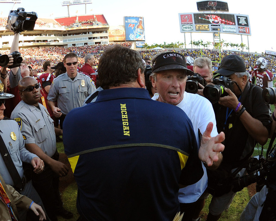 Description of . Coach Steve Spurrier of the South Carolina Gamecocks greets coach Brady Hoke of the Michigan Wolverines after play in the Outback Bowl January 1, 2013 at Raymond James Stadium in Tampa, Florida.  South Carolina won 33 - 28. (Photo by Al Messerschmidt/Getty Images)