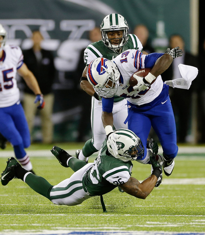 . New York Jets strong safety Dawan Landry (26) tackles Buffalo Bills wide receiver Stevie Johnson (13) during the second half of an NFL football game Sunday, Sept. 22, 2013, in East Rutherford, N.J. (AP Photo/Seth Wenig)