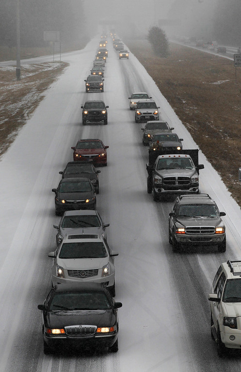 Description of . Vehicles moves slowly on Interstate 575 in North West Ga., Tuesday, Jan. 28, 2014, near Kennesaw, Ga. Georgians stocked up on ice-melting chemicals, school systems closed, and road crews prepared to clear snow and ice from highways as a winter storm took aim. (AP Photo/Mike Stewart)