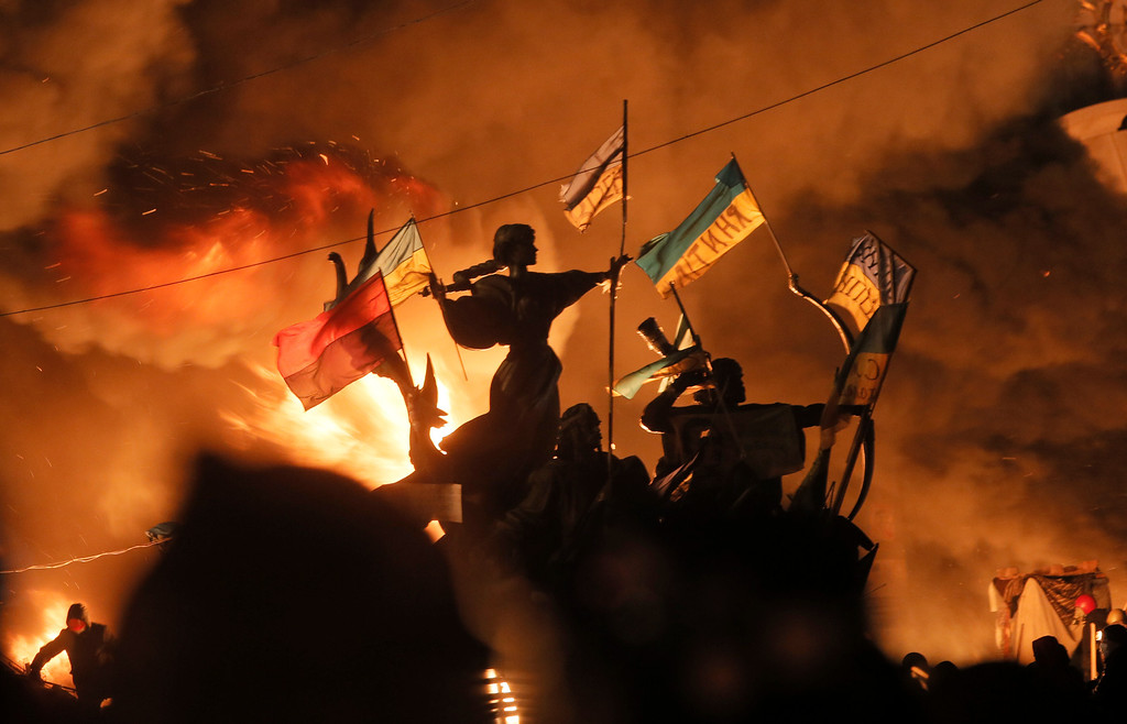 Description of . Monuments to Kiev's founders burn as anti-government protesters clash with riot police in Kiev's Independence Square, the epicenter of the country's current unrest,  Kiev, Ukraine, Tuesday, Feb. 18, 2014. (AP Photo/Efrem Lukatsky)