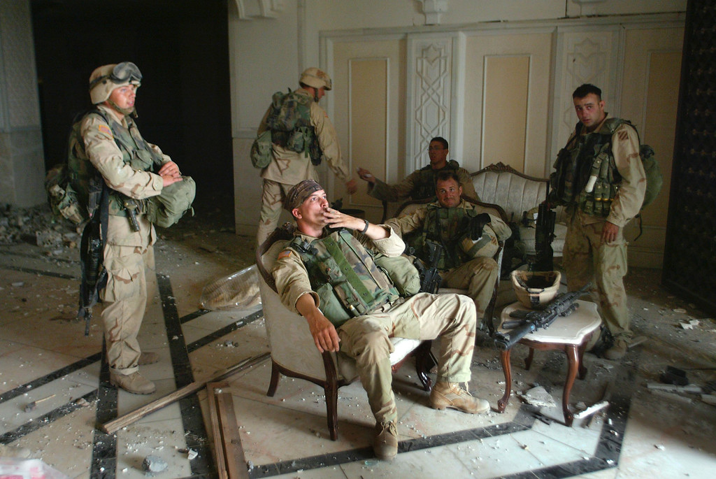 . U.S. Army Stf. Sgt. Chad Touchett, center, relaxes with comrades from A Company, 3rd Battalion, 7th Infantry Regiment, following a search in one of Saddam Hussein\'s damaged palaces on April 7, 2003 in Baghdad. (AP Photo/John Moore)