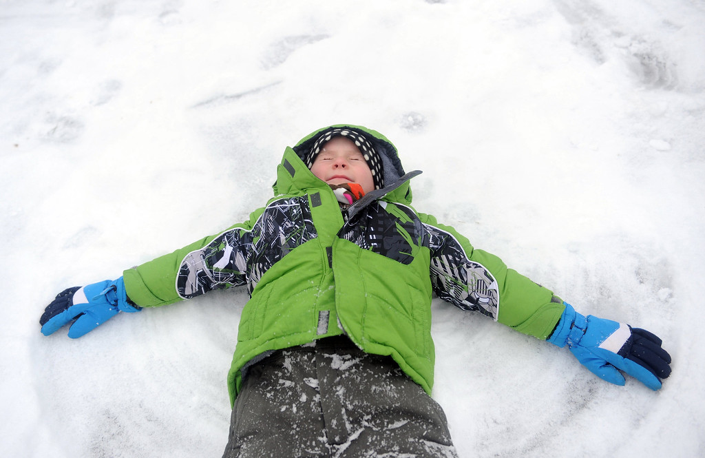 Description of . Evan Watson, 5, lays in the snow and makes a snow angel as his brothers play football with friends at their home  in Evansville, Ind.,  on Friday morning, Dec. 6, 2013.   (AP Photo/The Evansville Courier & Press, Erin McCracken)