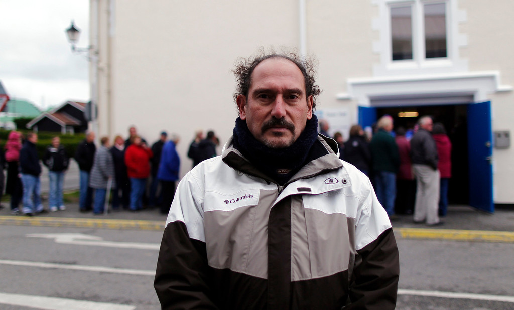 Description of . A veteran of the Falklands War, Gustavo Jimenez, poses for a picture as people line up to cast their vote at the Town Hall polling station in Stanley, March 10, 2013. Residents of the Falkland Islands started voting on Sunday in a sovereignty referendum that seeks to counter Argentina's increasingly assertive claim over the British-ruled territory. REUTERS/Marcos Brindicci