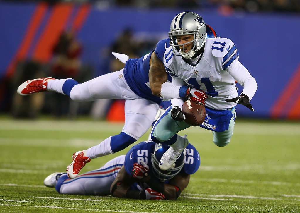 Description of . Cole Beasley #11 of the Dallas Cowboys is tackled against  Terrell Thomas #24 and  Jon Beason #52 of the New York Giants during their game at MetLife Stadium on November 24, 2013 in East Rutherford, New Jersey.  (Photo by Al Bello/Getty Images)