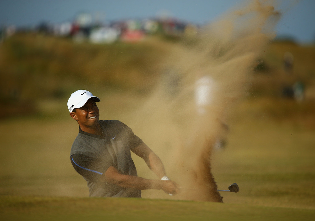Description of . GULLANE, SCOTLAND - JULY 20:  Tiger Woods of the United States plays out of a bunker on the 15th hole during the third round of the 142nd Open Championship at Muirfield on July 20, 2013 in Gullane, Scotland.  (Photo by Matthew Lewis/Getty Images)