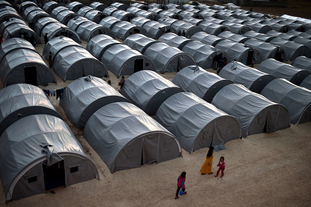 Description of . Syrian Kurdish refugees that fled the Syrian town of Kobane, also known as Ain al-Arab, walk past tents in a refugee camp in the southeastern town of Suruc, in the Turkish Sanliurfa province, on October 16, 2014. Kurdish fighters backed by a flurry of US-led air strikes were holding out on October 16 against jihadists in Kobane, as an Islamic State (IS) offensive on the Syrian border town entered its second month. ARIS MESSINIS/AFP/Getty Images