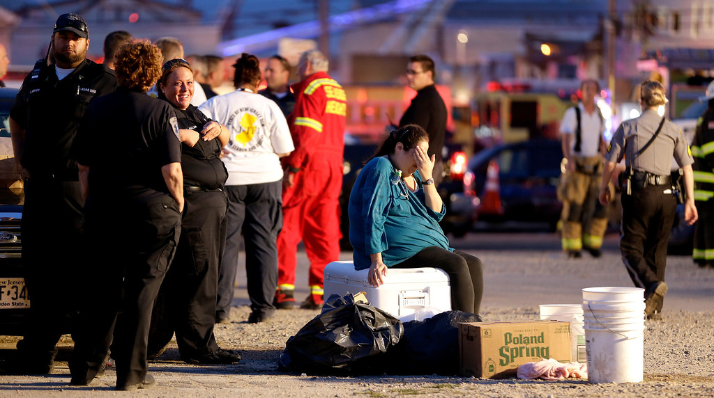 Description of . A woman puts her hand over her face as she sits on a cooler in an area for first responders working a massive fire at the Seaside Park boardwalk, Thursday, Sept. 12, 2013, in Seaside Park, N.J. The fire, which apparently started in an ice cream shop and spread several blocks, hit the recently repaired boardwalk, which was damaged last year by Superstorm Sandy. There were no other early reports of any injuries. (AP Photo/Julio Cortez)