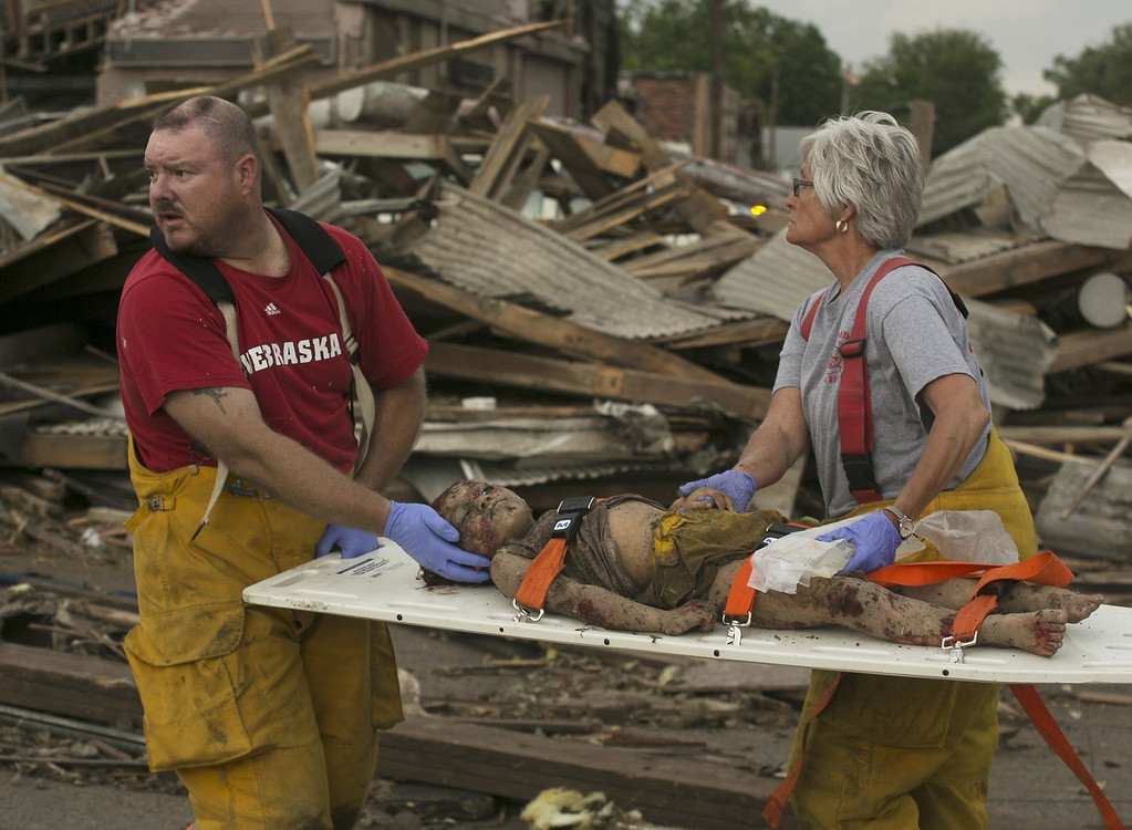Description of . Rescue personnel tend to a young tornado victim in  Pilger, Neb., Monday, June 16, 2014. A hospital spokeswoman says at least one person is dead and at least 16 more are in critical condition after two massive tornadoes swept through northeast Nebraska. (AP Photo/Mark \'Storm\' Farnik)