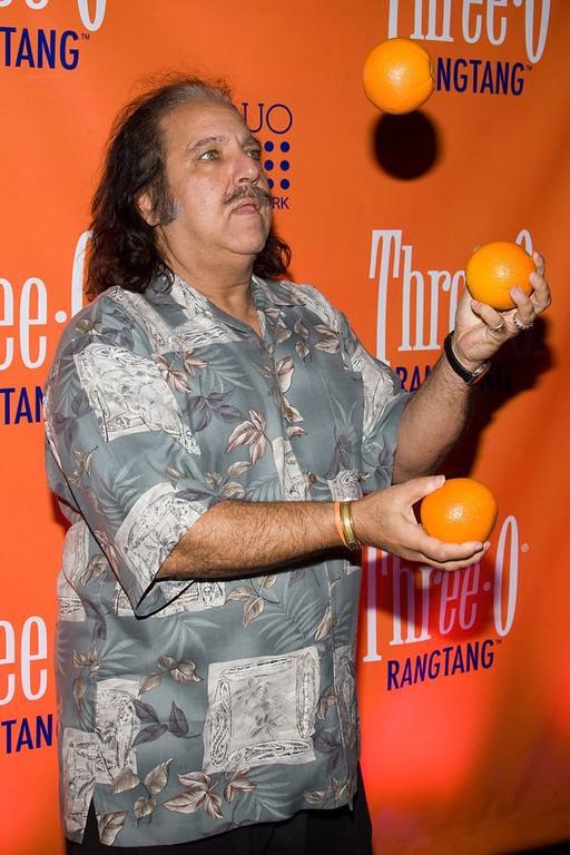 Description of . Ron Jeremy juggles oranges at the launch party for Three-O Vodka's new flavor
