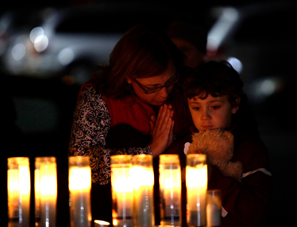 Description of . A woman and a child holding a teddy bear pray over candles outside Saint Rose of Lima Roman Catholic Church a day after a shooting at Sandy Hook Elementary School in Newtown, Connecticut December 15, 2012. Twelve girls, eight boys and six adult women were killed in the shooting on Friday at the Sandy Hook Elementary School in Newtown, Connecticut, the state's chief medical examiner said on Saturday. Dressed in