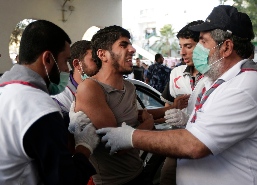 Description of . Palestinians assist a youth, wounded in an Israeli strike, into the emergency room at Shifa Hospital, in Gaza City, northern Gaza Strip,Thursday, July 31, 2014. (AP Photo/Lefteris Pitarakis)