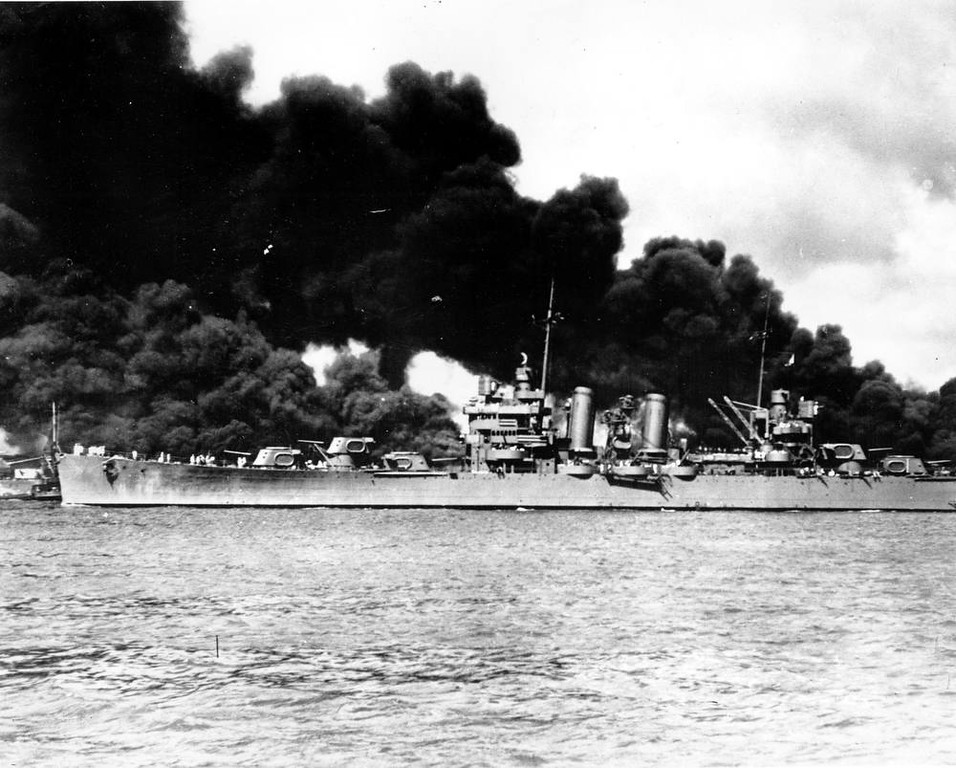 Description of . An undamaged light cruiser steams out past the burning USS Arizona and takes to sea with the rest of the fleet during the Japanese aerial attack on Pearl Harbor, Hawaii, on Dec. 7, 1941 during World War II.  (AP Photo/U.S. Navy)