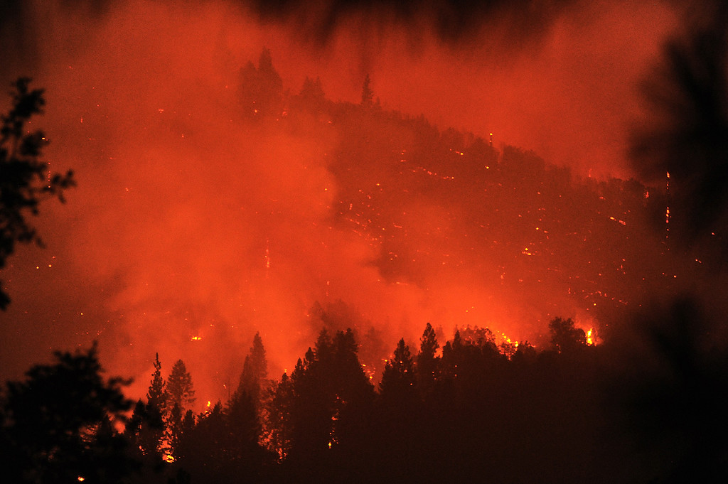 Description of . Smoke from the Rim Fire glows orange while a hillside smolders in a canyon of the South Fork of the Tuolumne in the Stanislaus National Forest Saturday Aug. 24, 2013.