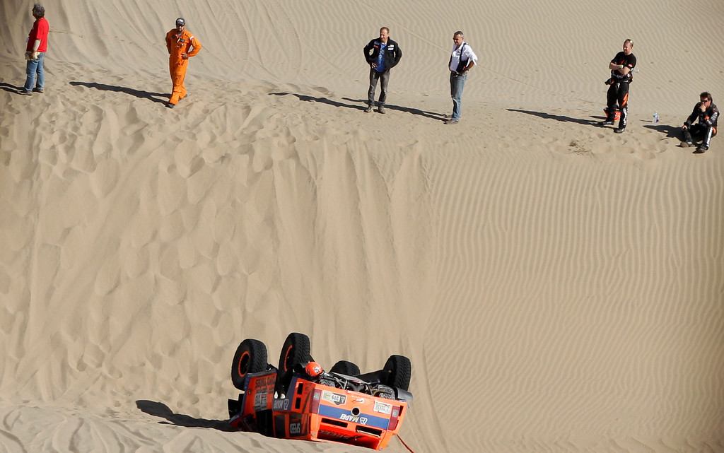 Description of . Hummer driver Robby Gordon, right, and co-driver Kellon Walch, second from right, both of the U.S., stand on a dune overlooking their overturned vehicle during the 4nd stage of the 2013 Dakar Rally from Nazca to Arequipa, Peru, Tuesday, Jan. 8, 2013. The race finishes in Santiago, Chile, on Jan. 20. Third from right is Dakar rally director Etienne Lavigne. (AP Photo/Victor R. Caivano)