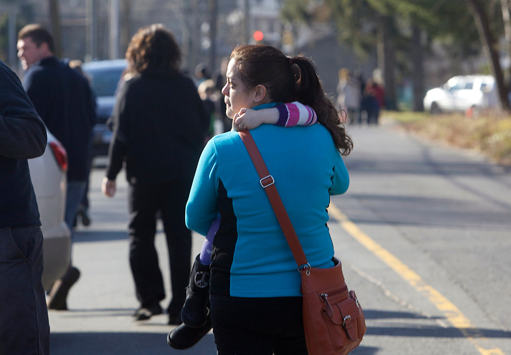 Description of . A woman carries her daughter following a shooting at Sandy Hook Elementary School in Newtown, Connecticut, December 14, 2012. A shooter opened fire at the elementary school in Newtown, Connecticut, on Friday, killing several people including children, the Hartford Courant newspaper reported. REUTERS/Michelle McLoughlin