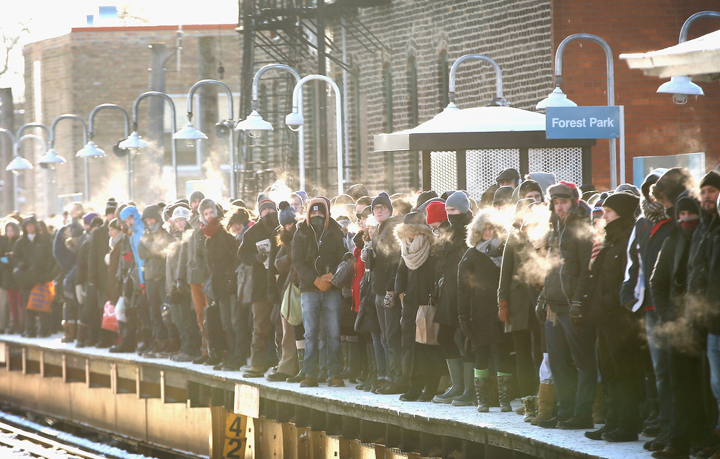 ". Passengers heading into downtown wait on an ""L\"" platform for the train to arrive in below zero temperatures on January 7, 2014 in Chicago, Illinois. Platforms were crowded and trains were delayed because doors on the trains kept freezing open. Chicago is experiencing its third consecutive day of below zero temperatures.  (Photo by Scott Olson/Getty Images)"
