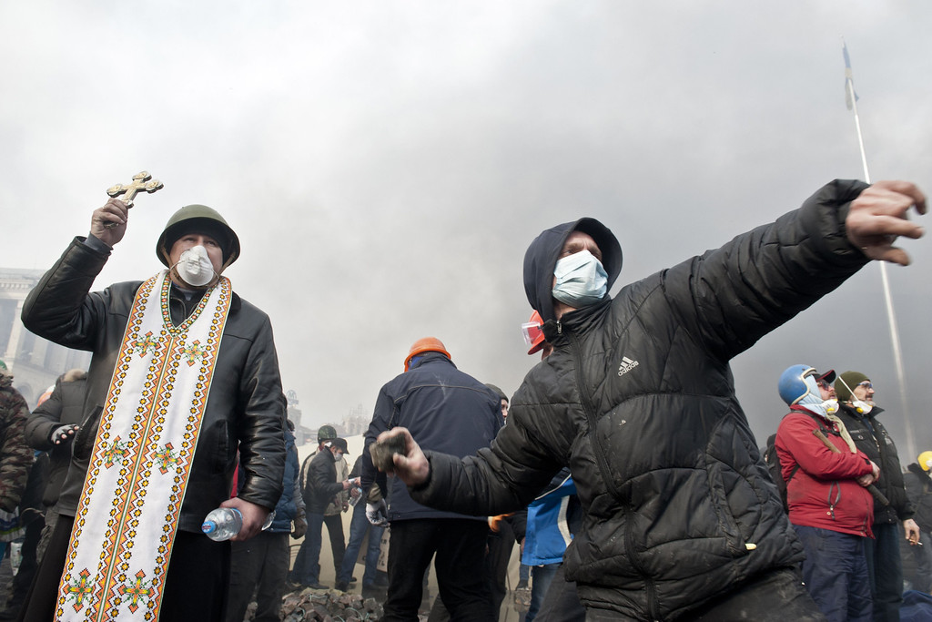 Description of . An anti-government protester prepares to throw a stone at riot police while another holds up a cross during clashes on Kiev's Independence square on February 19, 2014.  AFP PHOTO / PIERO  QUARANTA/AFP/Getty Images