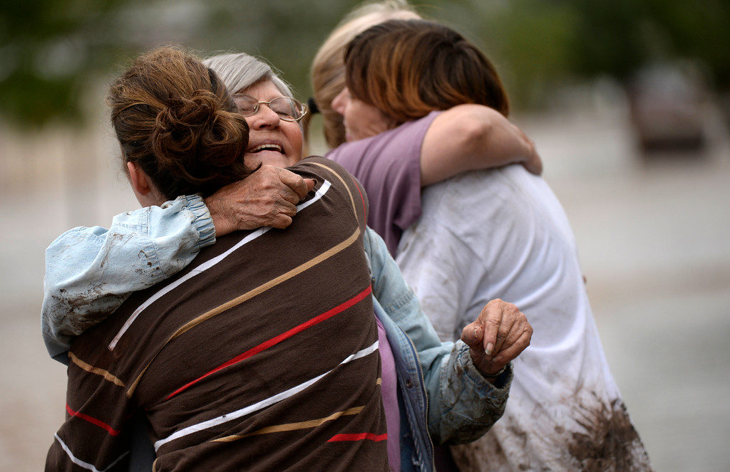 Description of . EVANS, CO - SEPTEMBER 16: Virginia Tucker, second from the left, gets hugs from friends and family after getting to dry ground in Evans, September 16, 2013. Massive flooding continues to hit Colorado. (Photo By RJ Sangosti/The Denver Post)
