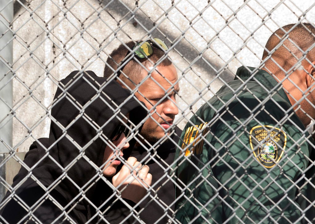 . Pop singer Justin Bieber, left, is escorted out of the Turner Guilford Knight Correctional Center, Thursday Jan. 23, 2014 in Doral, Fla., following his arrest earlier in the day in Miami Beach. Bieber was arrested and charged with driving under the influence and resisting arrest after police said they saw him speeding down a residential street in a yellow Lamborghini. Officers say he had an expired license, was initially not cooperative when he was pulled over, and smelled of alcohol. (AP Photo/Wilfredo Lee)