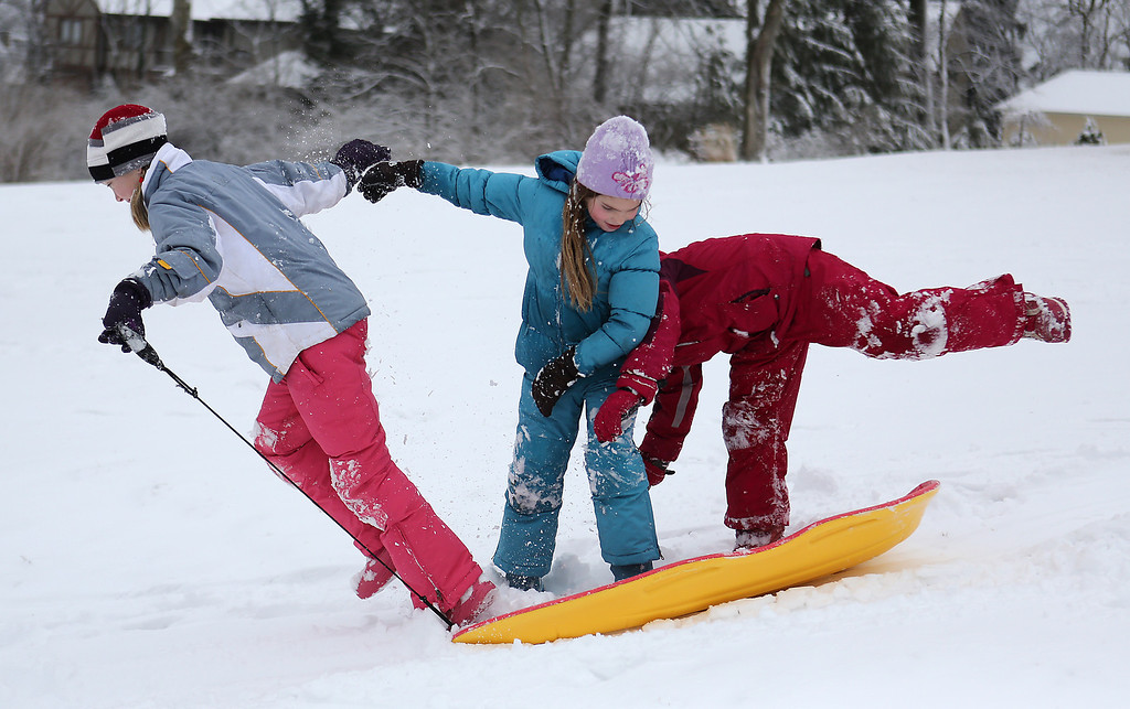 Description of . From left,  Maeve Talty, 10, Caroline Talty, 8, and Maureen Greenwell, 8, all from Mt. Lookout, Ohio, try to stay on a sled together at the Cincinnati Observatory Center in Hyde Park on Wednesday, March 6, 2013.    Hundreds of schools including in some of Ohio's biggest public districts called off classes Wednesday. (AP Photo/The Cincinnati Enquirer, Leigh Taylor)