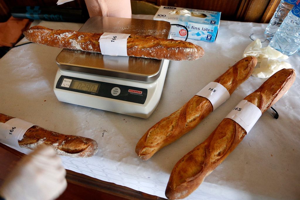 Description of . An assistant weighs baguettes, French bread, registered in the competition for the 'Grand Prix de la Baguette de la Ville de Paris' (Best Baguette of Paris 2013) annual prize at the Chambre Professionnelle des Artisans Boulangers Patissiers in Paris April 25, 2013. The baguette is a French cultural symbol par excellence and the competition saw 203 Parisian bakers who compete for recognition as finest purveyor of one of France's most iconic staples. The baguettes are registered, given anonymous white wrappings and an identification number. They are then carefully weighed and measured to ensure they do not violate the contest's strict rules. 52 entries were withdrawn for failing to measure between 55-70cm long or not matching the acceptable weight of between 250-300g. Every year, the winner earns the privilege of baking bread for the French President.   REUTERS/Charles Platiau