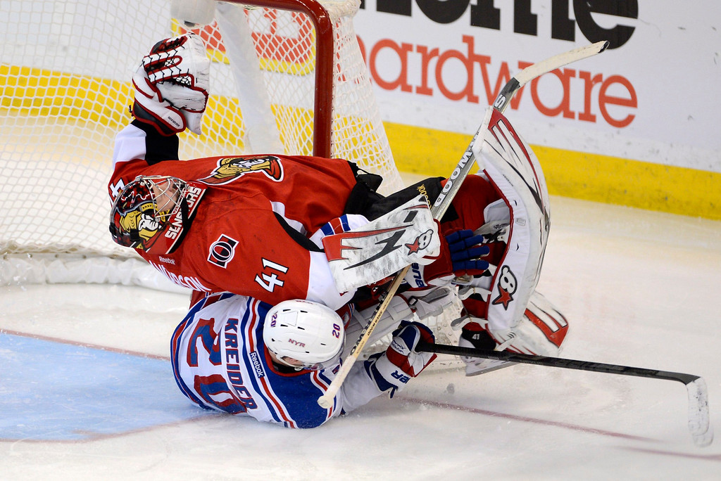 Description of . Ottawa Senators goalie Craig Anderson is taken down New York Rangers\' Chris Kreider during the third period of an NHL hockey game in Ottawa, Ontario, Thursday, Feb. 21, 2013. (AP Photo/The Canadian Press, Adrian Wyld)