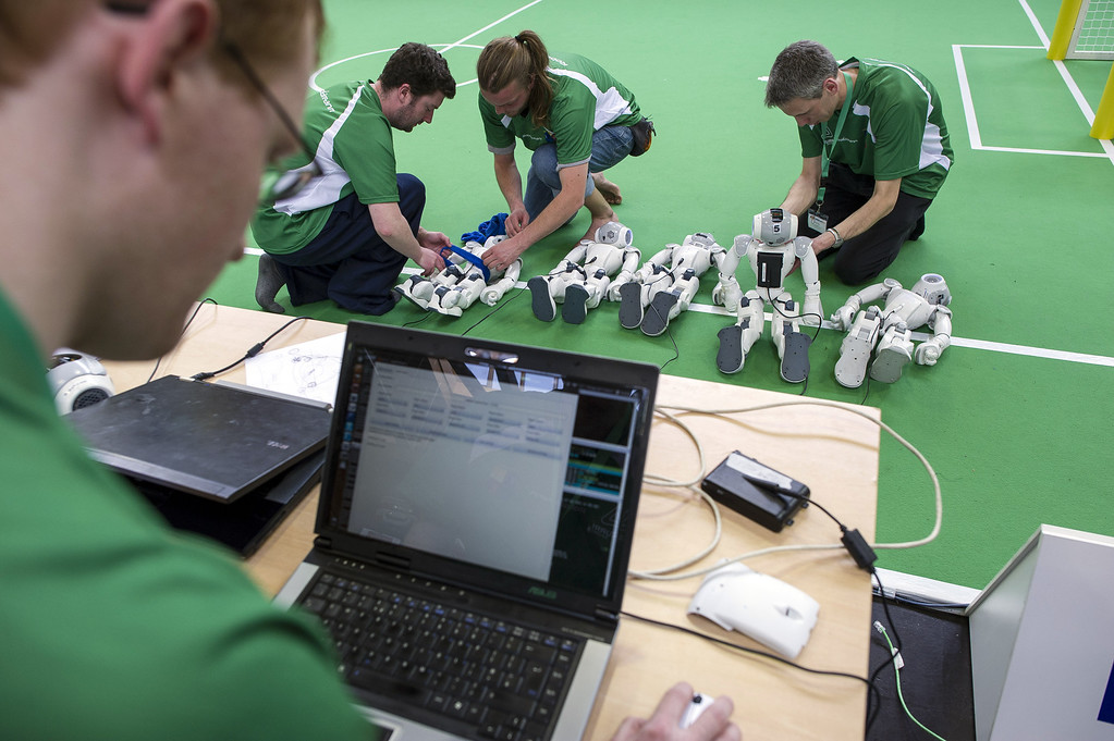 Description of . MAGDEBURG, GERMANY - APRIL 26:  Participants check robots at the 2013 RoboCup German Open tournament on April 26, 2013 in Magdeburg, Germany. The robots, which are a model called Nao, manufactured by Aldebaran Robotics, perform autonomously and communicate with one another via WLAN. The three-day tournament is hosting 43 international teams and 158 German junior teams that compete in a variety of disciplines, including soccer, rescue and dance.  (Photo by Jens Schlueter/Getty Images)