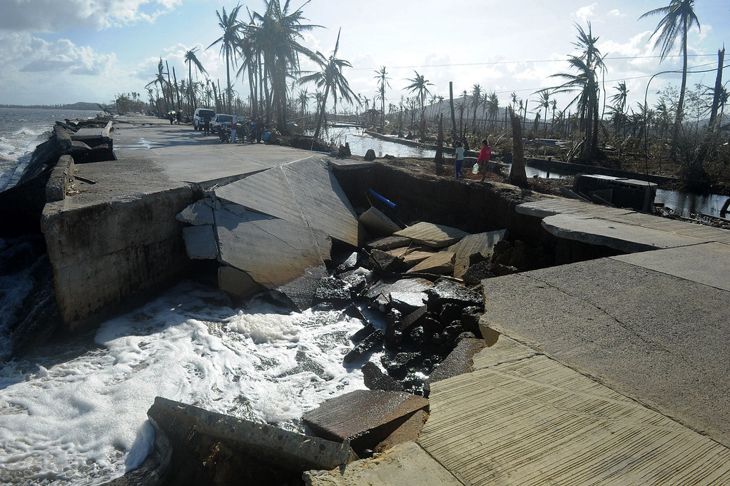 Description of . Residents cross a collapsed highway caused by the storm surge in Palo, eastern island of Leyte on November 10, 2013, three days after devastating Super Typhoon Haiyan hit the area on November 8. The death toll from a super typhoon that decimated entire towns in the Philippines could soar well over 10,000, authorities warned on November 10, making it the country's worst recorded natural disaster.  NOEL CELIS/AFP/Getty Images