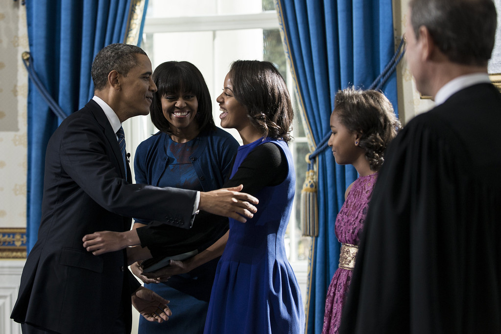 Description of . U.S. President Barack Obama hugs daughter Malia after being officially sworn-in as first lady Michelle Obama (C), daughter Sasha (2nd R) and Chief Justice John Robets Jr. watch in the Blue Room of the White House during the 57th Presidential Inauguration January 20, 2013 in Washington, D.C.  Obama and U.S. Vice President Joe Biden were officially sworn in a day before the ceremonial inaugural swearing-in. (Photo by Brendan Smialowski-Pool/Getty Images)