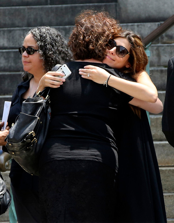 Description of . Actress Jamie Lynn Sigler, right, is embraced as she leaves the Cathedral Church of Saint John the Divine after the funeral service for James Gandolfini, Thursday, June 27, 2013 in New York.   (AP Photo/Mary Altaffer)