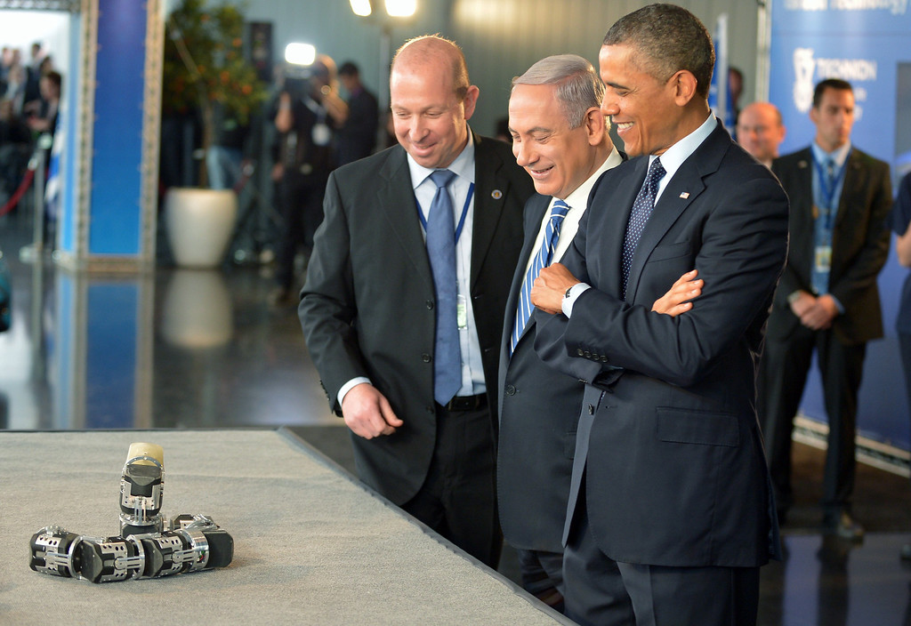 Description of . US President Barack Obama (R) and Israel's Prime Minister Benjamin Netanyahu (C) look at a snake-shaped robot which can be used in search and rescue operations during a tour of a technology exposition at the Israel Museum in Jerusalem on Mach 21, 2013.  AFP PHOTO/Mandel NGAN/AFP/Getty Images