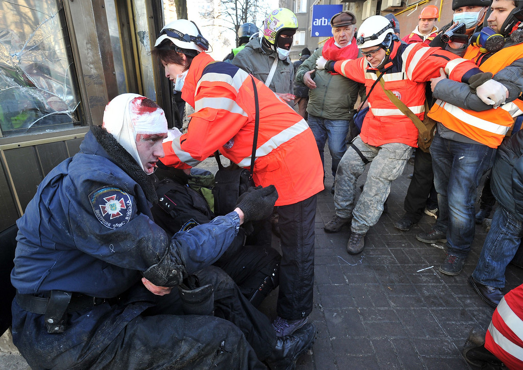Description of . Red Cross workers give first aid to policemen wounded during clashes with anti-government protester in Kiev on February 18, 2014. AFP PHOTO/GENYA SAVILOV/AFP/Getty Images