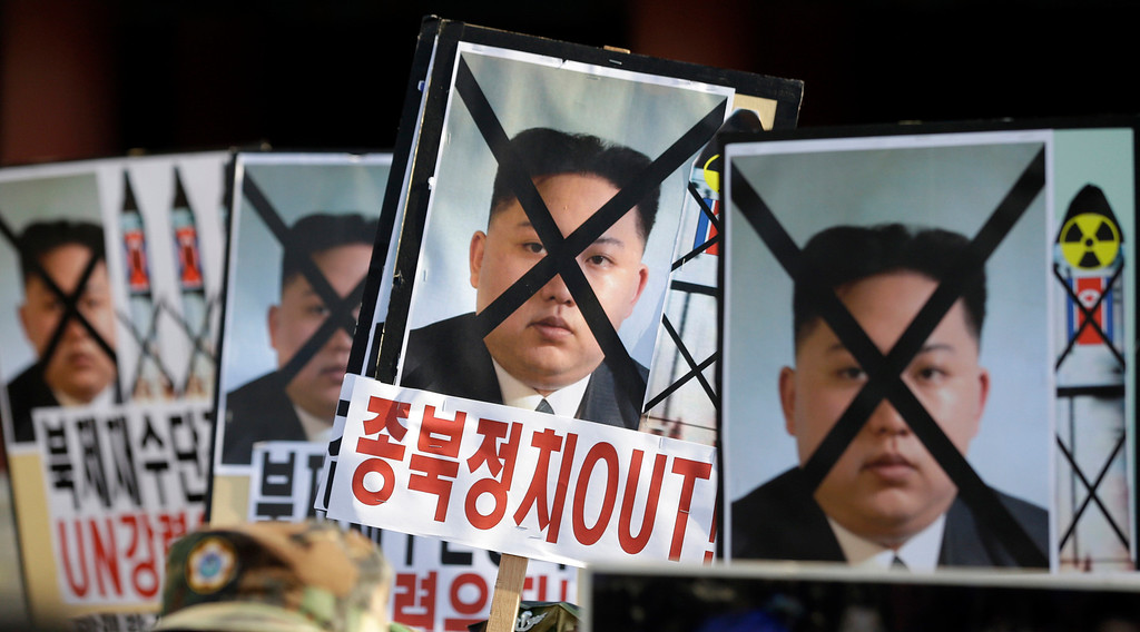 ". South Korean protesters hold the pictures of North Korean leader Kim Jong Un during a rally denouncing North Korea\'s rocket launch in Seoul, South Korea, Wednesday, Dec. 12, 2012. North Korea successfully fired a long-range rocket on Wednesday, defying international warnings as the regime of Kim Jong Un took a giant step forward in its quest to develop the technology to deliver a nuclear warhead. The letters read ""Out, Pro-North Korea politic.\"" (AP Photo/Lee Jin-man)"