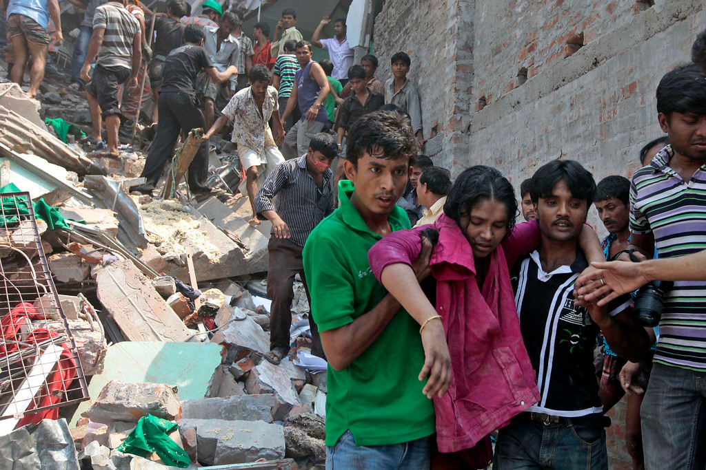 Description of . Rescuers assist an injured woman after an eight-story building housing several garment factories collapsed in Savar, near Dhaka, Bangladesh, Wednesday, April 24, 2013.  (AP Photo/ A.M. Ahad)