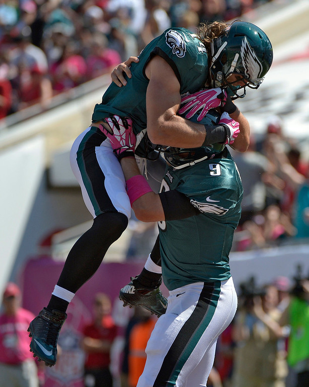 Description of . Philadelphia Eagles quarterback Nick Foles (9) celebrates with wide receiver Riley Cooper (14) after Foles scored on a four-yard touchdown run against the Tampa Bay Buccaneers during the first quarter of an NFL football game Sunday, Oct. 13, 2013, in Tampa, Fla. (AP Photo/Phelan M. Ebenhack)