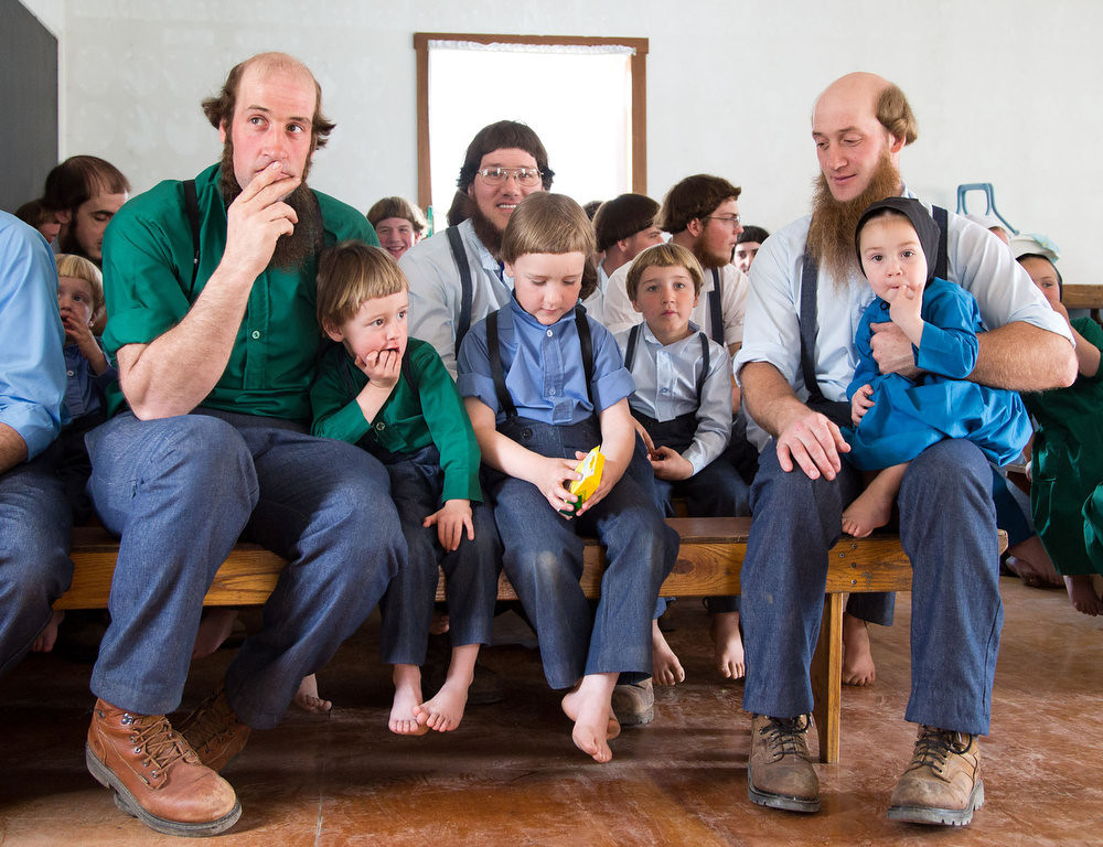 Description of . Amish men fill-up the school house to listen to their children sing during the final day of class on Tuesday, April 9, 2013 in Bergholz, Ohio. (AP Photo/Scott R. Galvin)