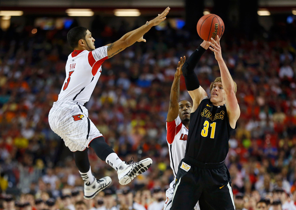 Description of . Wichita State Shockers guard Ron Baker (R) is guarded by Louisville Cardinals' Peyton Siva (L) and Russ Smith (rear) in the first half of their NCAA men's Final Four basketball game in Atlanta, Georgia April 6, 2013. REUTERS/Jeff Haynes
