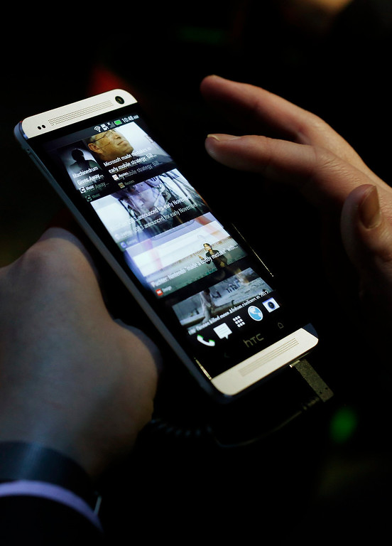 Description of . An attendee tests the new HTC One during a launch event in New York, February 19, 2013. REUTERS/Brendan McDermid