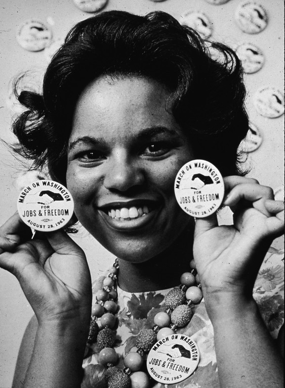 Description of . A female demonstrator smiles as she holds protest buttons next to her face at the March on Washington, Washington, DC, August 28, 1963. (Photo by Hulton Archive/Getty Images)